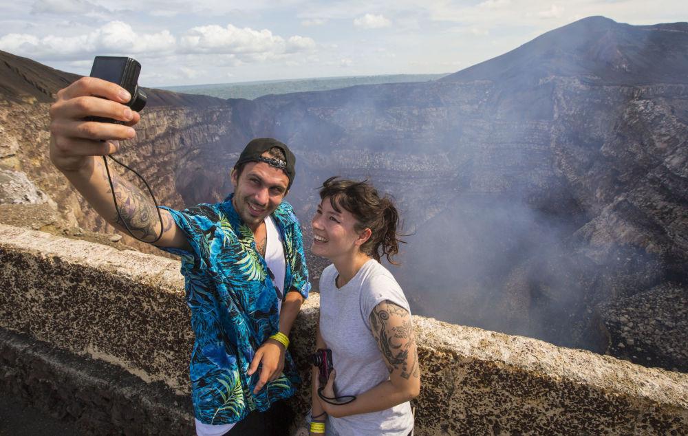 سياح يلتقطون صور سيلفي على خلفية بركان ماسايا، على بعد 30 كلم من مانغوا، نيكاراغوا