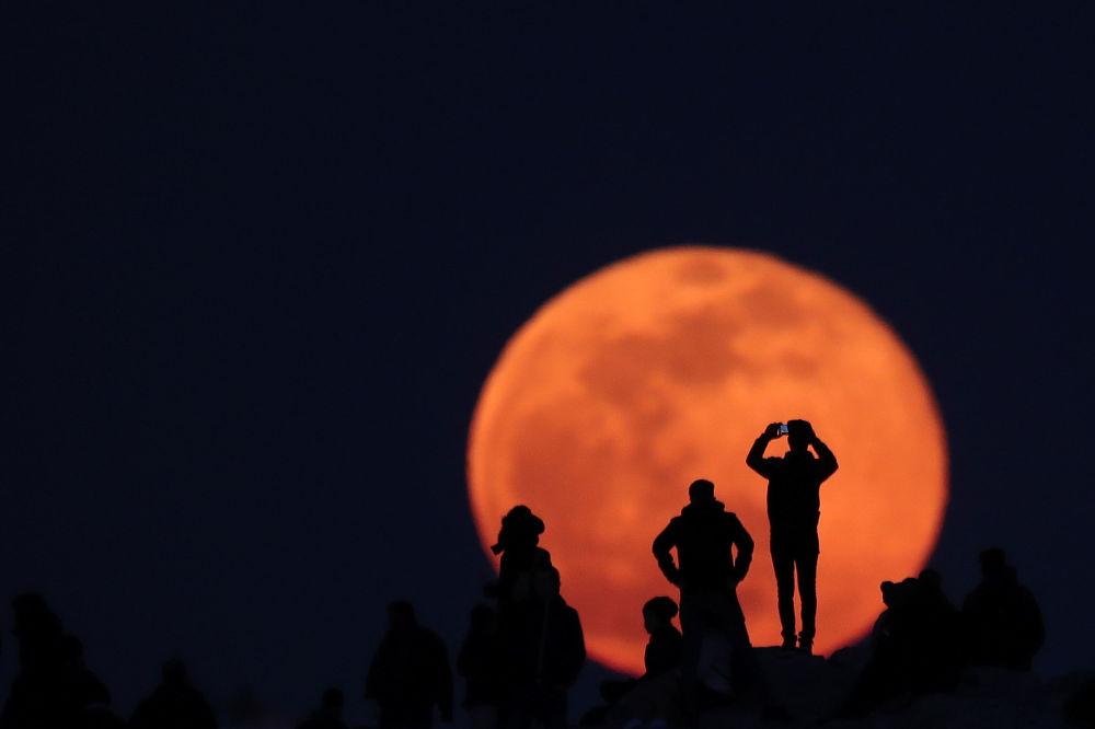 أشخاص يراقبون ارتفاع القمر الكامل من الموقع الأثري أكروبول في أثينا، اليونان 9 فبراير 2020