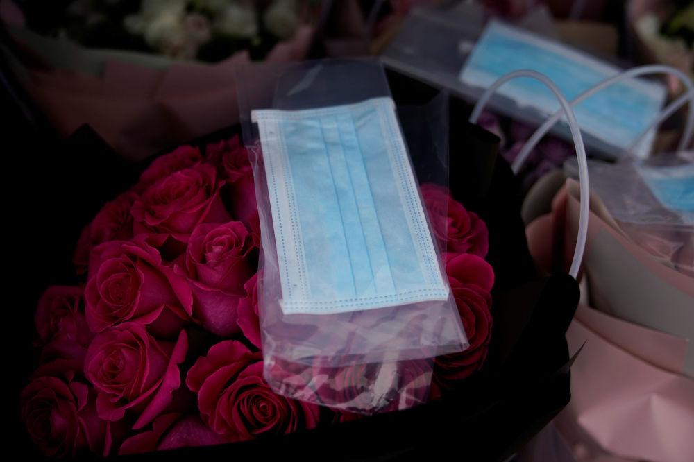 قناع واقي على باقة زهور في متجر لبيع الزهور بمناسبة يوم فالنتاين (عيد الحب) في شنغهاي، الصين 14 فبراير 2020