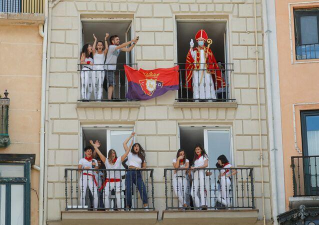 متجول يرتدي زي القديس فيرمين يلوح بيده من الشرفة أمام المدينة حيث كان من المفترض أن يفتح مهرجان سان فيرمين الملغي بسبب تفشي مرض (كوفيد-19)، في بامبلونا، إسبانيا 6 يوليو 2020.
