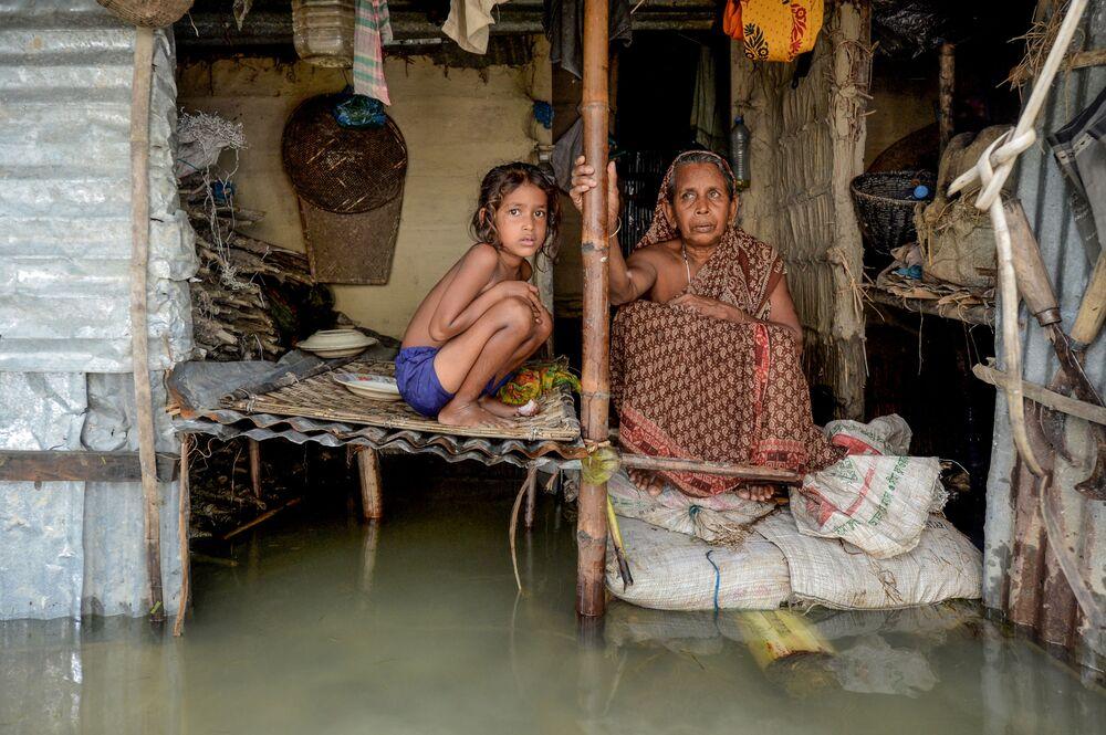 فيضانات آسيا، فتاة تجلس بجوار امرأة في بنغلادش، بعد الفيضانات الكبيرة التي أصابت معظم مناطق آسيا 16 يوليو 2020