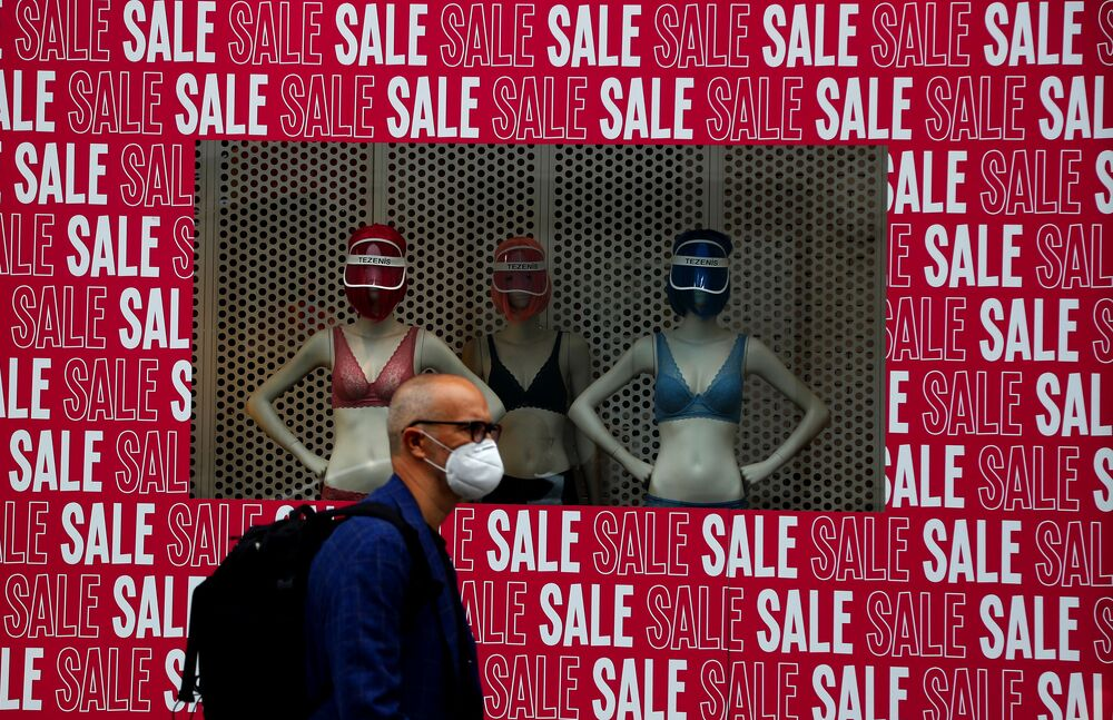 رجل يرتدي كمامة يسير أمام نافذة متجر في لندن، 14 يوليو 2020. تطالب الحكومة البريطانية المواطنين بارتداء الكمامات داخل المتاجر حيث سعت لتوضيح رسالتها بعد أسابيع من المراوغة وسط وباء كوفيد-19 .