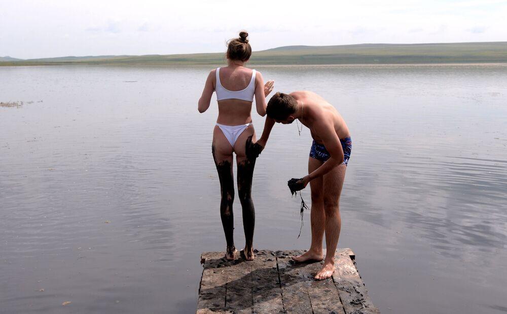 رجل يضع طين الكبريتيد على جسم المرأة من بحيرة طوس في منطقة شيرينسكي بجمهورية خاكاسيا الروسية، 13 يوليو 2020