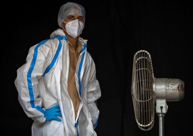 موظف من القطاع الصحي يأخذ استراحة أثناء انتظار الناس لجمع عينات لإجراء اختبارات لمرض الفيروس التاجي (كوفيد-19)، وسط انتشار الوباء في نيودلهي، الهند  10 يوليو 2020.