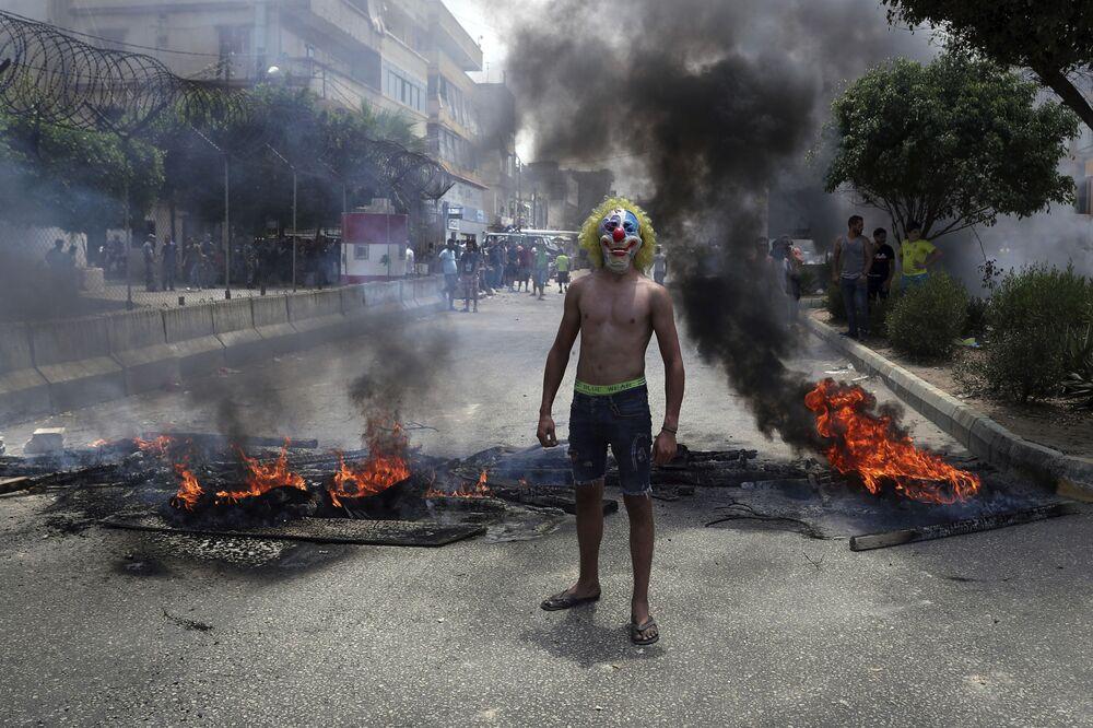 متظاهر مناهض للحكومة يرتدي قناع مهرج بينما يقوم آخرون بحرق الإطارات والخشب لإغلاق طريق في بيروت، في إطار احتجاجات عارمة في لبنان لسوء الأحوال الاقتصادية في البلاد، 14 يوليو 2020.