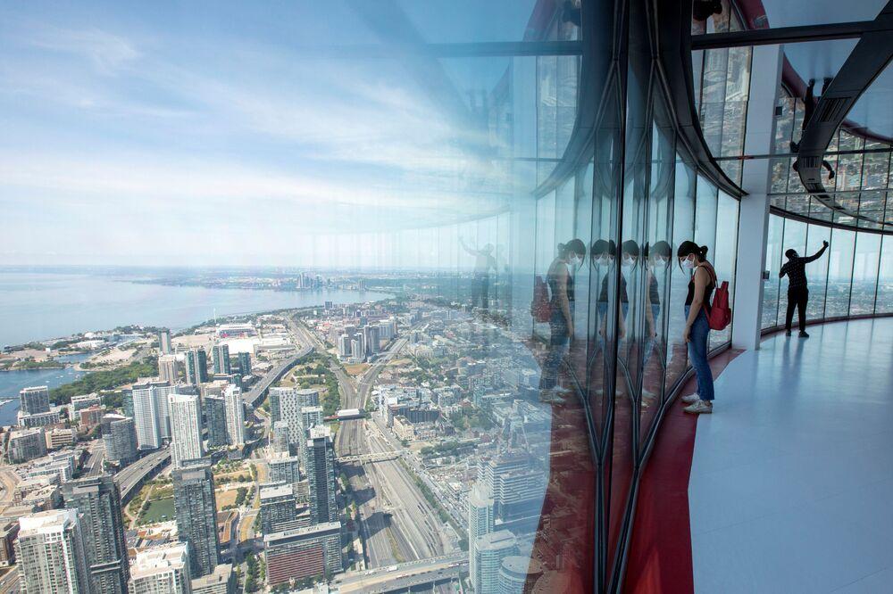 يشاهد الزائرون مشاهد المدينة البانورامية من برج سي إن الذي يبلغ ارتفاعه 553 مترًا (1815 قدمًا) ، والذي أعيد افتتاحه لأول مرة منذ فرض قيود منع المرض التاجي (كوفيد-19) في تورونتو ، أونتاريو، كندا 15 يوليو 2020.