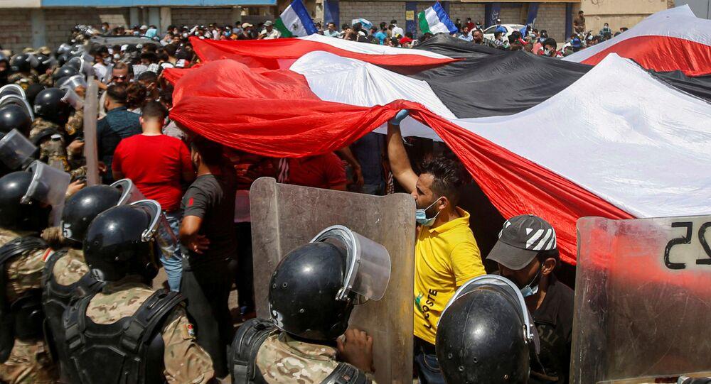 قوات الأمن العراقية تقف أمام متظاهرين في احتجاجات مناهضة للحكومة أثناء زيارة رئيس الوزراء العراقي مصطفى الكاظمي إلى البصرة، العراق، 15 يوليو 2020.