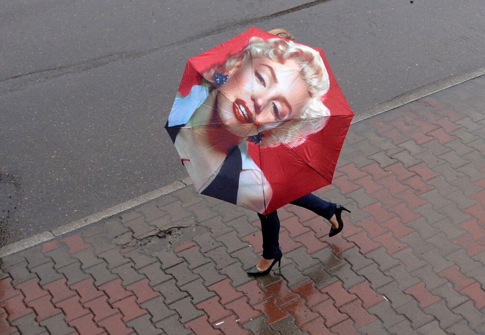 امرأة تحمل مظلة مرسوم عليها الفنانة ميرلين مونرو وتسير في الشارع أثناء عاصفة ممطرة في كراسنويارسك الروسية، 10 يوليو 2020