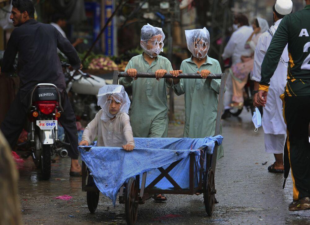 صبيان يغطون وجوههم بأكياس بلاستيكية أثناء دفع عربة يد أثناء هطول الأمطار في بيشاور، باكستان 12 يوليو 2020