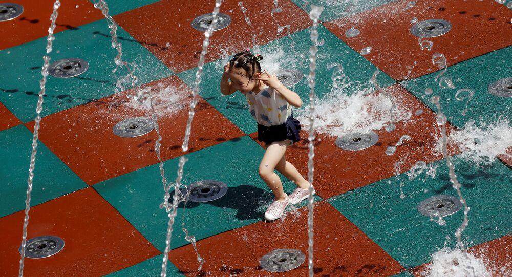 فتاة تلعب بمياه النافورة في يوم صيفي حار في مجمع للتسوق في بكين، الصين 14 يوليو 2020