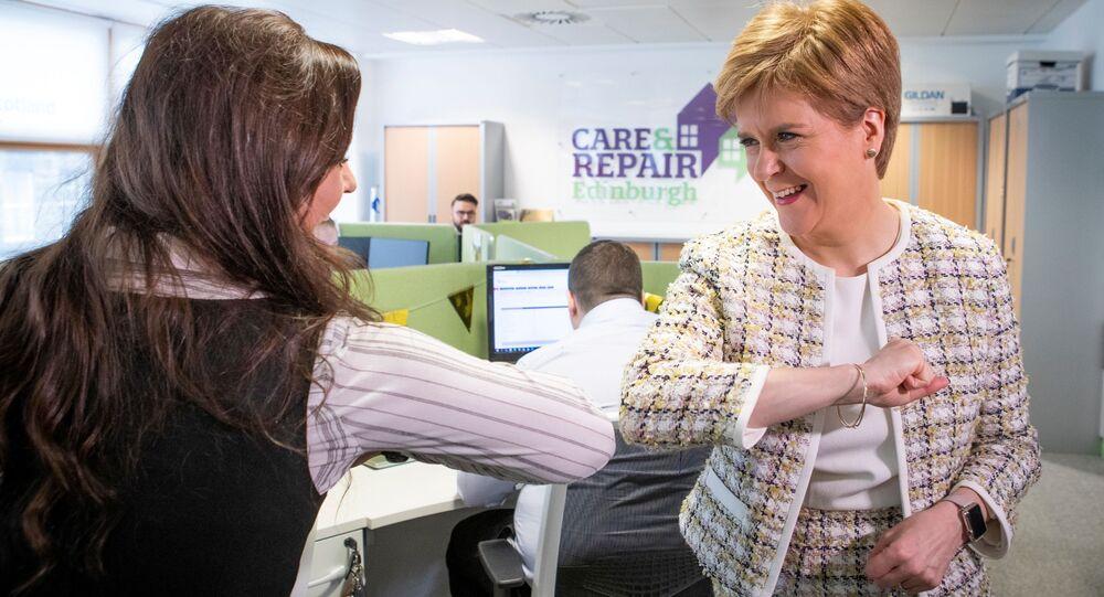 الوزيرة الأولى لاسكتلندا نيكولا ستارجن  (يمين) تلقي التحية بكوعها خلال زيارتها لمكتب الاتصالات الطارئة (خط المساعدة للمسنين في اسكتلندا المدعوم من الحكومة الاسكتلندية) في إطار مكافحة وباء كورونا، في أدنبره في 18 مارس 2020