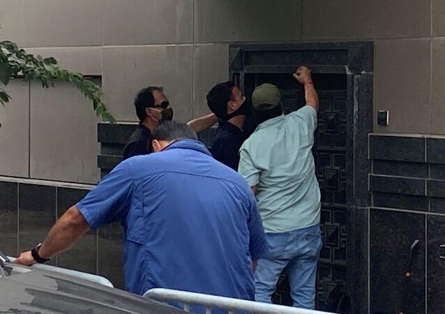 مجموعة من الأشخاص يستخدمون أدوات كهربائية لمحاولة فتح باب خلفي للقنصلية الصينية في هيوستن