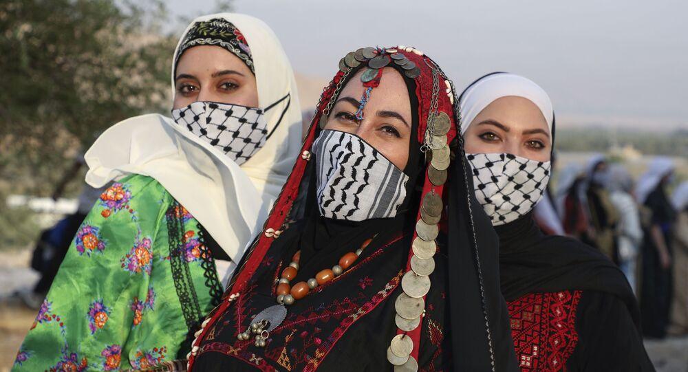 فتيات فلسطينيات يرتدين الثوب الفلسطيني، و كمامات على شكل كوفية، احتفالا بيوم الزي الفلسطيني في قرية الجفتلك وادي الأردن، 26 يوليو 2020