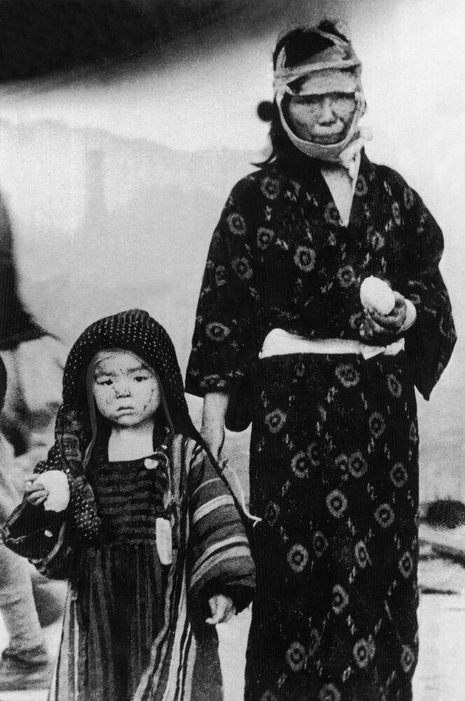 صورة من الأرشيف - امرأة يابانية مع طفلها يرتديان ملابس يابانية تقليدية، بعد نجاتهما من القنبلة الذرية التي ألقيت على ناغازاكي، بتاريخ 9 أغسطس/ آب 1945.