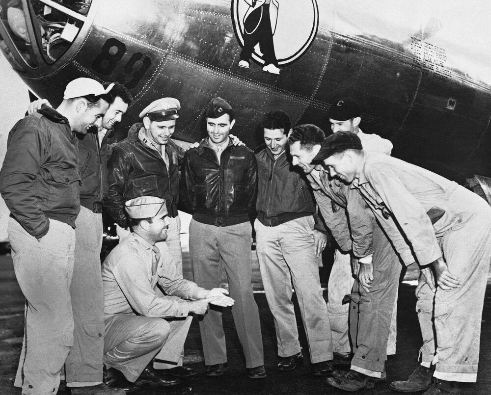 الطيارون الأمريكيون، المشاركون في قصف مدينتي هيروشيما وناغازاكي، يقفون على خلفية طائرة بي-29 في نورث كوينسي، ماساتشوستس، 8 نوفمبر/ تشرين الثاني 1945