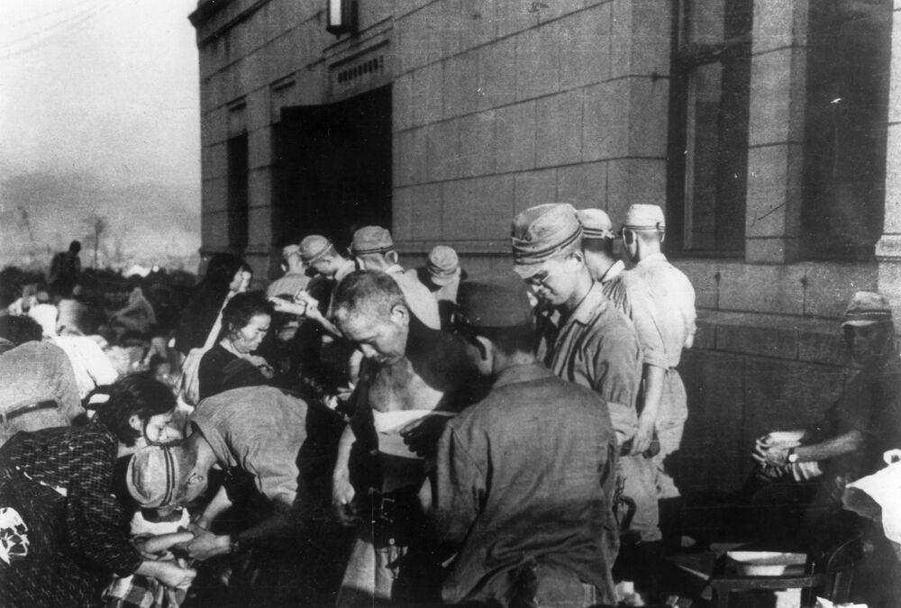 صورة بتاريخ 6 أغسطس/ آب عام 1945 - يظهر فيها الجرحى والمصابين في هيروشيما، الذين يتلقون المساعدة الأولية والعلاج  من قبل القوات العسكرية اليابانية في أغسطس/ آب 1945