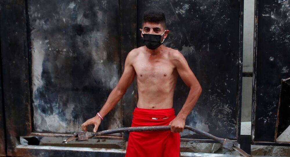 متظاهر يرتدي كمامة واقية من فيروس كورونا ويحمل قضيبا معدنيا خلال مظاهرة في بيروت بعد الانفجار الذي هز المدينة