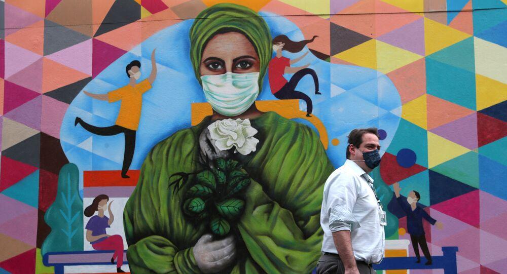 رجل يسير بجوار جدارية عن تأبين ضحايا الأطقم الطبية جراء فيروس كورونا المستجد في سان باولو بالبرازيل