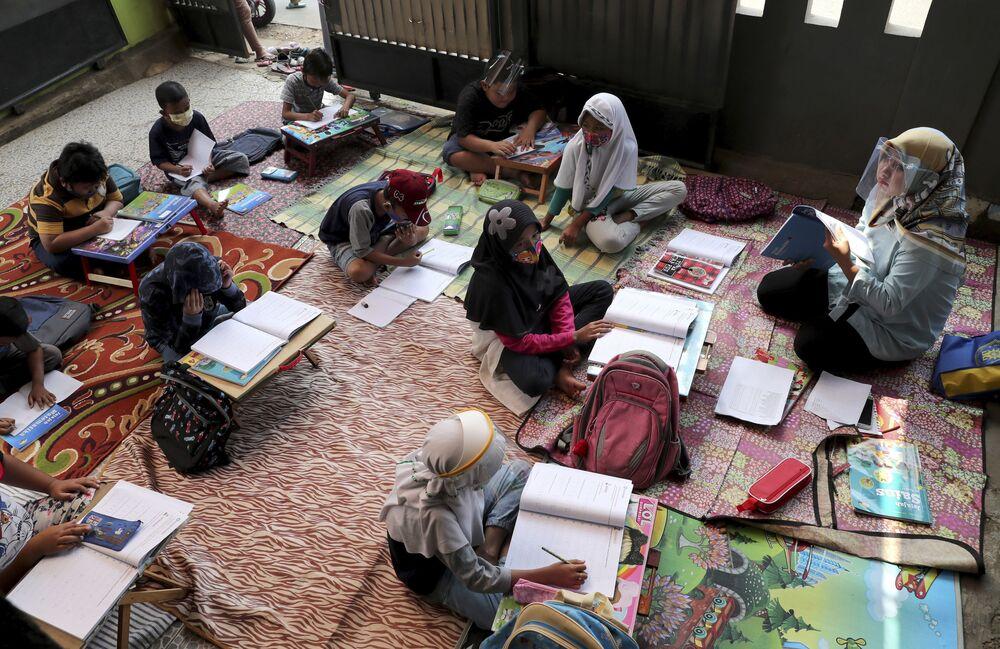 المعلمة والتلاميذ يرتدون كمامات طبية أثناء الدرس في تانغيرانغ، في إطار الاجراءات الاحترازية لمنع تفشي فيروس كورونا، إندونيسيا 10 أغسطس 2020