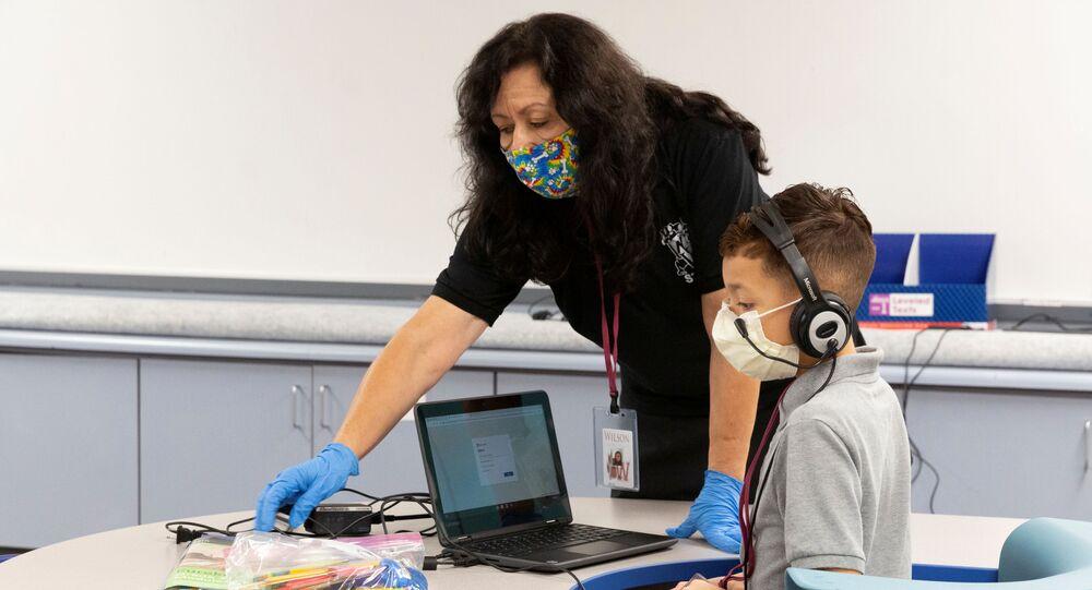 مساعد معلم والتلميذ يرتديان كمامات طبية في مدرسة في فينيكس، في إطار الاجراءات الاحترازية لمنع تفشي فيروس كورونا، ولاية أريزونا، الولايات المتحدة 16أغسطس 2020