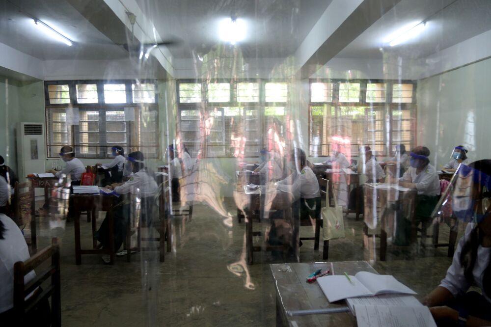تلاميذ يجلسون خلاف مقاعد دراسية محاطة بحواجز بلاستيكية شفافة في مدرسة في يانغون، في إطار الاجراءات الاحترازية لمنع تفشي فيروس كورونا، اليابان 21 يوليو 2020