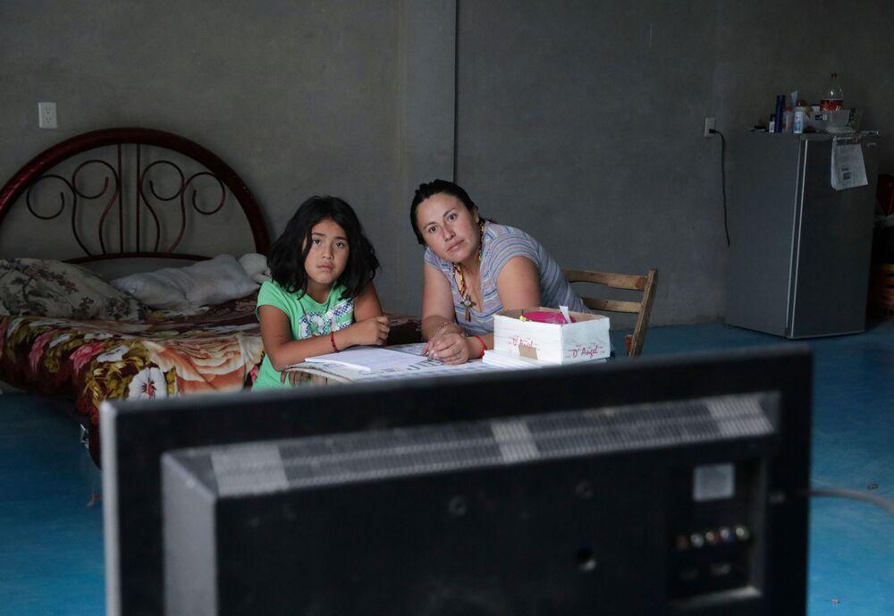 أم تساعد طفلتها أثناء الدرس عن بعد، في إطار الاجراءات الاحترازية لمنع تفشي فيروس كورونا، المكسيك 24 أغسطس 2020