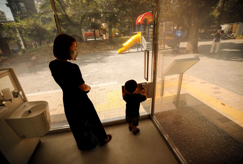 أم مع طفلها داخل مرحاض بجدران شفافة في حديقة يويوجي فوكاماتشي ميني بارك في طوكيو، اليابان 26 أغسطس 2020