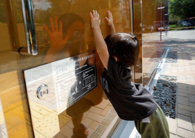 طفل ينظر إلى أمه عبر الجدران الشفافة لمرحاض عام في حديقة يويوجي فوكاماتشي ميني بارك في طوكيو، اليابان 26 أغسطس 2020