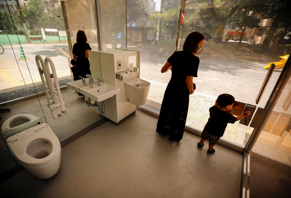 أم مع طفلها يتفقدان المرحاض بالجدران الشفافة في حديقة يويوجي فوكاماتشي ميني بارك في طوكيو، اليابان 26 أغسطس 2020
