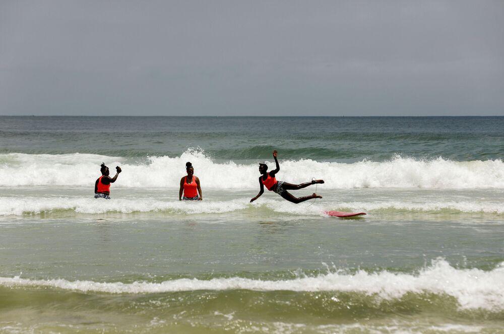 الفتاة السنغالية خادجو سامبي، 25 عاما، أول امرأة محترفة في ركوب الأمواج في السنغال، خلال تدريب الفتيات على ركوب الأمواج في دكار 28 يوليو/ تموز  2020