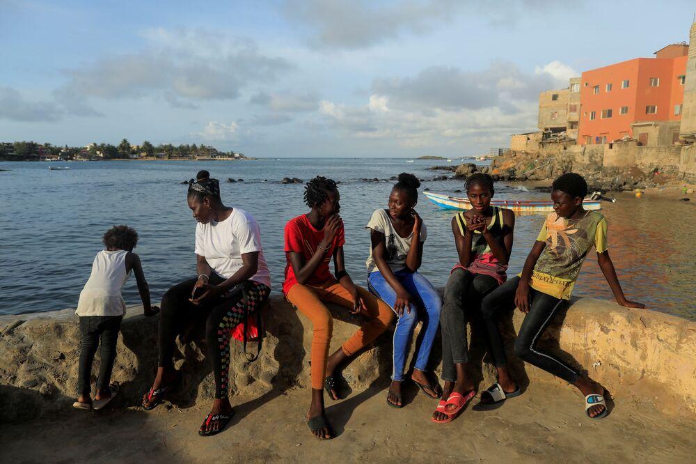 الفتاة السنغالية خادجو سامبي، 25 عاما، أول امرأة محترفة في ركوب الأمواج في السنغال، برفقة فريق التدريب، في دكار 30 يوليو/ تموز  2020