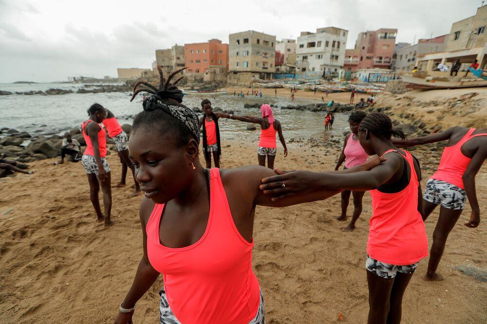 الفتاة السنغالية خادجو سامبي، 25 عاما، أول امرأة محترفة في ركوب الأمواج في السنغال، أثناء تدريب الفتيات على ركوب الأمواج، في دكار 3 أغسطس/ آب 2020