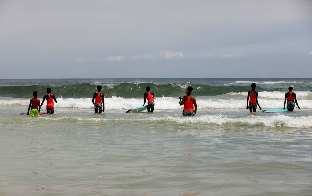 الفتاة السنغالية خادجو سامبي، 25 عاما، أول امرأة محترفة في ركوب الأمواج في السنغال، أثناء تدريب الفتيات على ركوب الأمواج، في دكار 28  يوليو/ تموز 2020