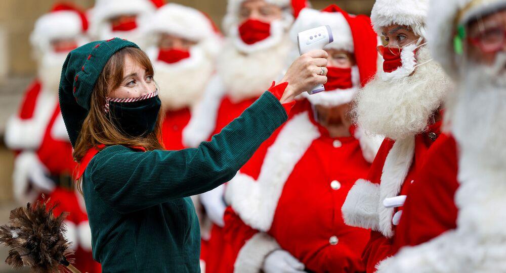 امرأة ترتدي زي قزم تتفقد درجات حرارة خريجي مدرسة سانتا كلوز التابعة لوزارة المرح  خارج كاتدرائية ساوثوارك في لندن، بريطانيا، 24 أغسطس  2020.