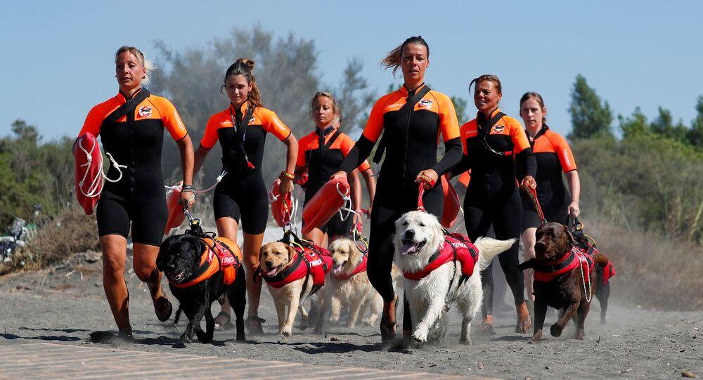 طاقم الإنقاذ مع الكلاب المرافقة من المدرسة الإيطالية كلاب الإنقاذ (La Scuola Italiana Cani Salvataggio) يحضرن جلسة تدريبية مع كلابهن قبل القيام بدوريات على الشاطئ، للتأكد من أن السباحين يمكنهم الاستمتاع بوقتهم في البحر بأمان، في منطقة ريفا دي تاركويني بالقرب من روما، إيطاليا، 25 أغسطس 2020.