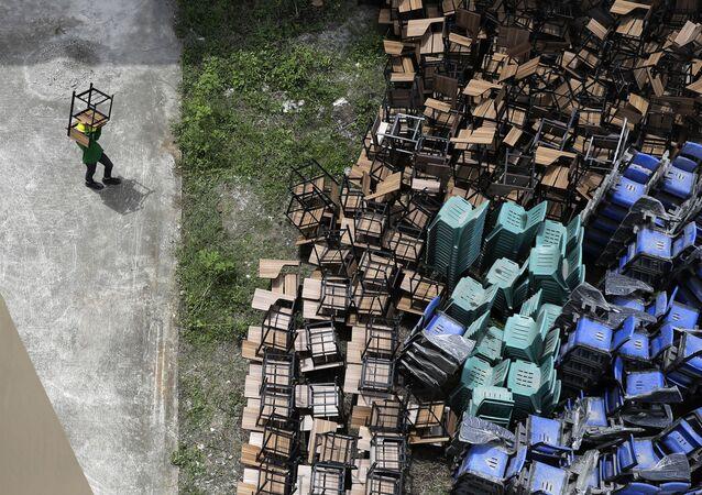 موظف مدرسة ابتدائية يقوم بتجهيز المقاعد الدراسية قبل بدء العام الدراسي في مدينة كزون، وقد تم استخدام الفصول الدراسية سابقا لاستقبال مرضى كوفيد - 19، الفلبين 1 سبتمبر 2020