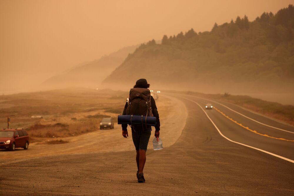 رجل يسير على طريق ريدوود السريع على خلفية سماء برتقالية اللون، بسبب حرائق الغابات الهائلة في ولاية كاليفورنيا، 9 سبتمبر 2020