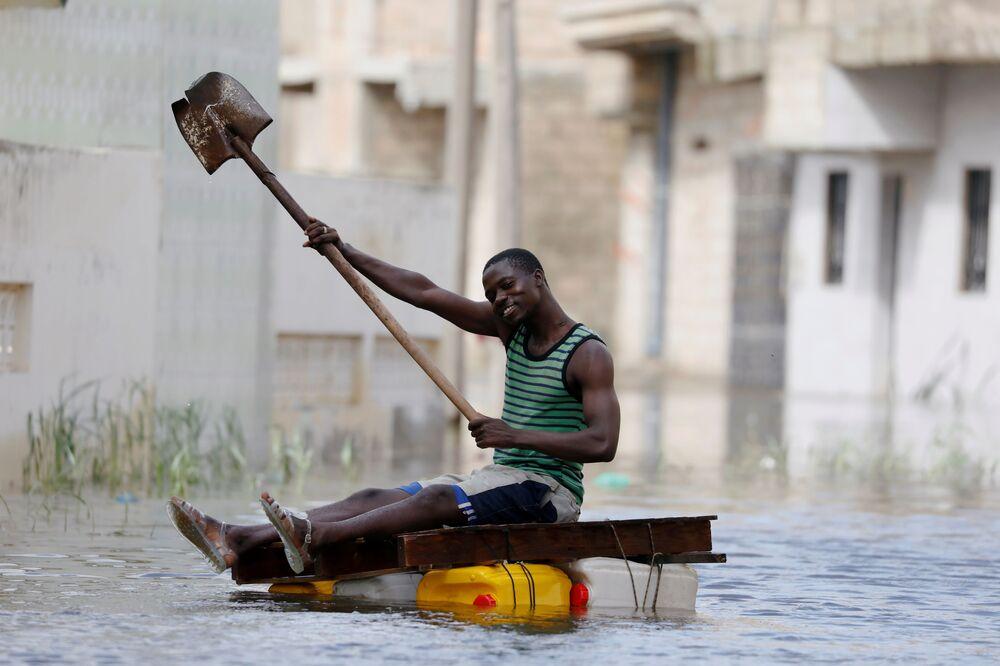 أحد أهالي مدينة كور-مساري يركب طوفا مؤقتا في الشوارع التي غمرتها المياه بعد هطول أمطار غزيرة، السنغال 9 سبتمبر 2020