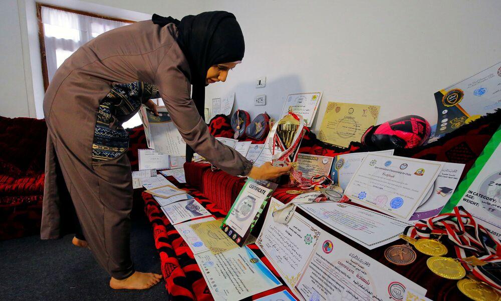مدربة الفنون القتالية وبطلة الكيك بوكسينج اليمنية سهام عامر تعرض شهاداتها و ميدالياتها في منزلها في صنعاء، اليمن 3 سبتمبر 2020