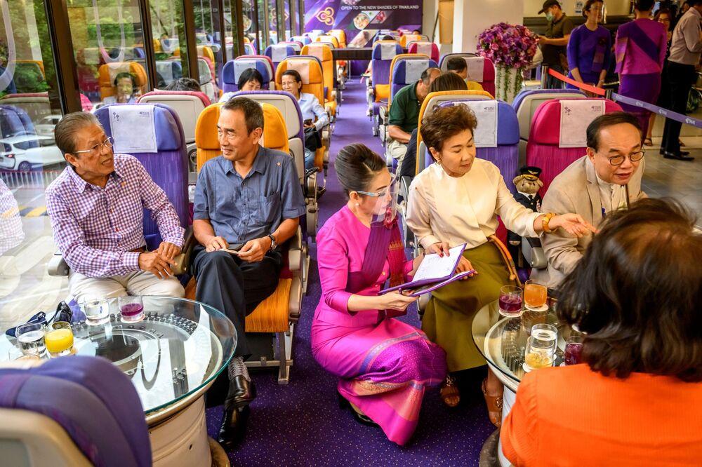 مضيفة طيران الخطوط الجوية التايلاندية أثناء خدمة زوار مطعم على متن طائرة في بانكوك، 10 سبتمبر 2020