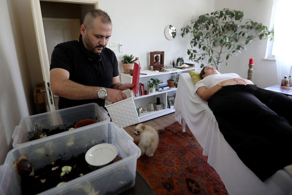 سهيل سويدان، 34 عاماً، يقوم بتحضير الحلزونات البرية الأفريقية العملاقة قبل البدء بجلسة تدليك الوجه، التي تعتبر مصدراً لتعزيز مادة الكولاجين في الجلد، في مركز تجميل في عمان، الأردن، 16 سبتمبر / أيلول 2020