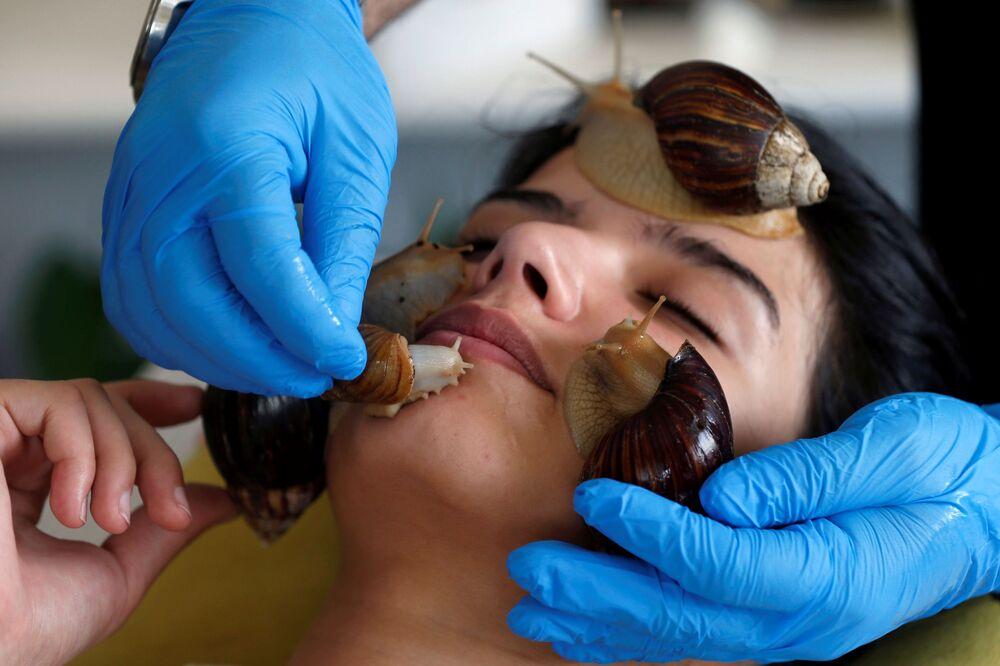 نورما رشية، 22 عاماً، خلال جلسة تدليك الوجه بواسطة الحلزونات البرية الأفريقية العملاقة، التي تعتبر مصدراً لتعزيز مادة الكولاجين في الجلد، في مركز تجميل في عمان، الأردن، 16 سبتمبر / أيلول 2020