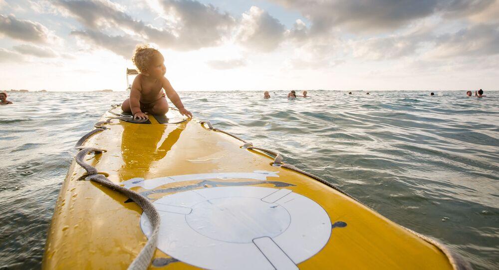 طفل على لوح لركوب الأمواج في المحيط