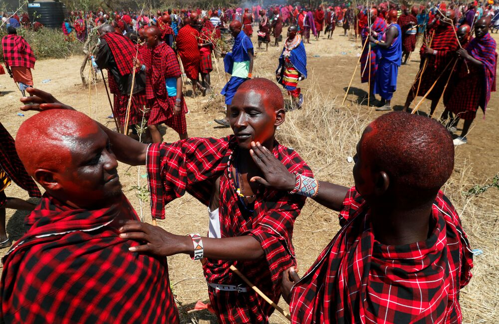 رجال قبيلة ماساي يزينون أنفسهم بصبغة حمراء قبل السير على درب أكل اللحوم، ليلتحم هناك دربين: درب الكبار إلبامو (Ilpaamu) والشباب إلايتي (Ilaitete)، أثناء احتفالات أولنغيشير (Olng'esherr) عند تلال ماباراشا، بالقرب من كاجيادو في كينيا، 23 سبتمبر 2020