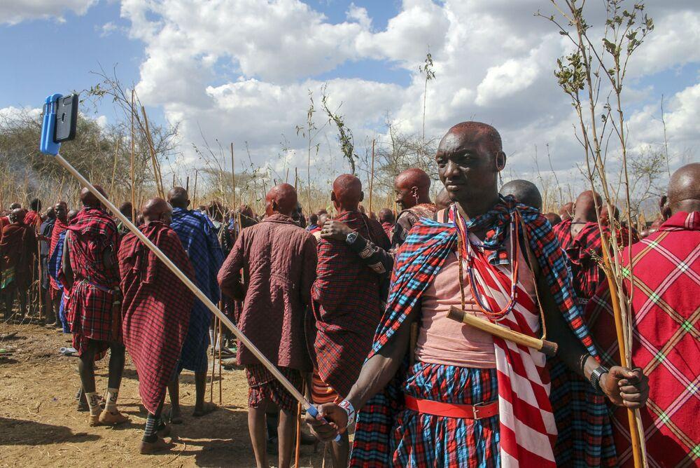 أحد أفراد قبيلة ماساي موران (أو المحارب) يلتقط صورة سيلفي، حيث يشارك هو وآخرون في احتفالات أولنغيشير (Olng'esherr) عند تلال ماباراشا، بالقرب من كاجيادو في كينيا، 23 سبتمبر  2020