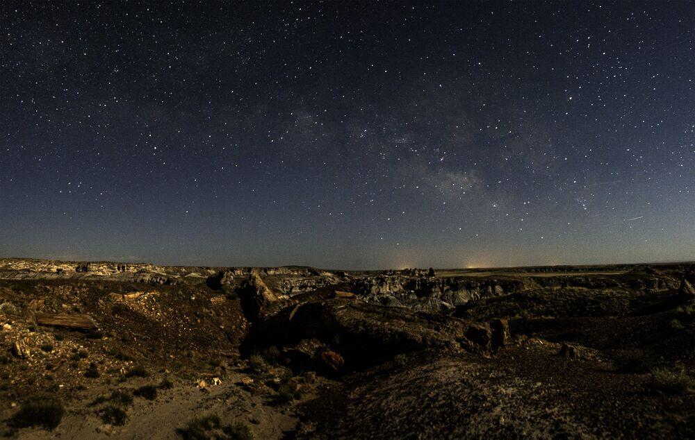 السماء المرصعة بالنجوم فوق حديقة الغابة المتحجرة الوطنية بيتريفايد فوريست في ولاية أريزونا، الولايات المتحدة