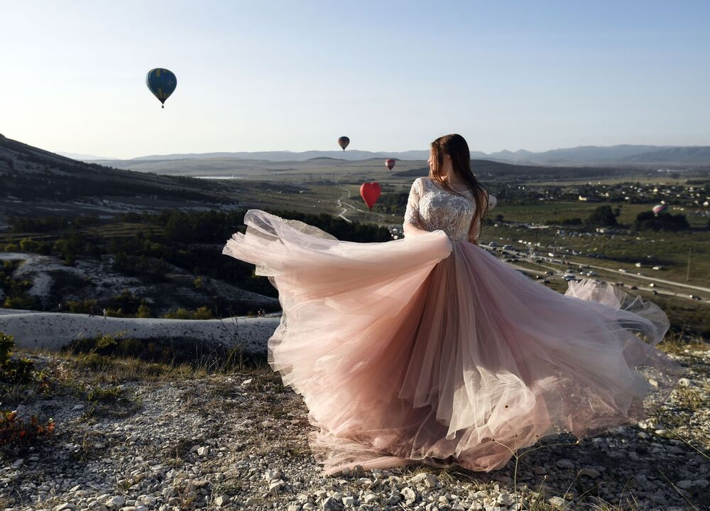 فتاة في مهرجان للمناطيد الهوائية عند سفح المنحدر الصخري الأبيض في منطقة بيلوغورسك بجمهورية القرم، روسيا 19 سبتمبر 2020