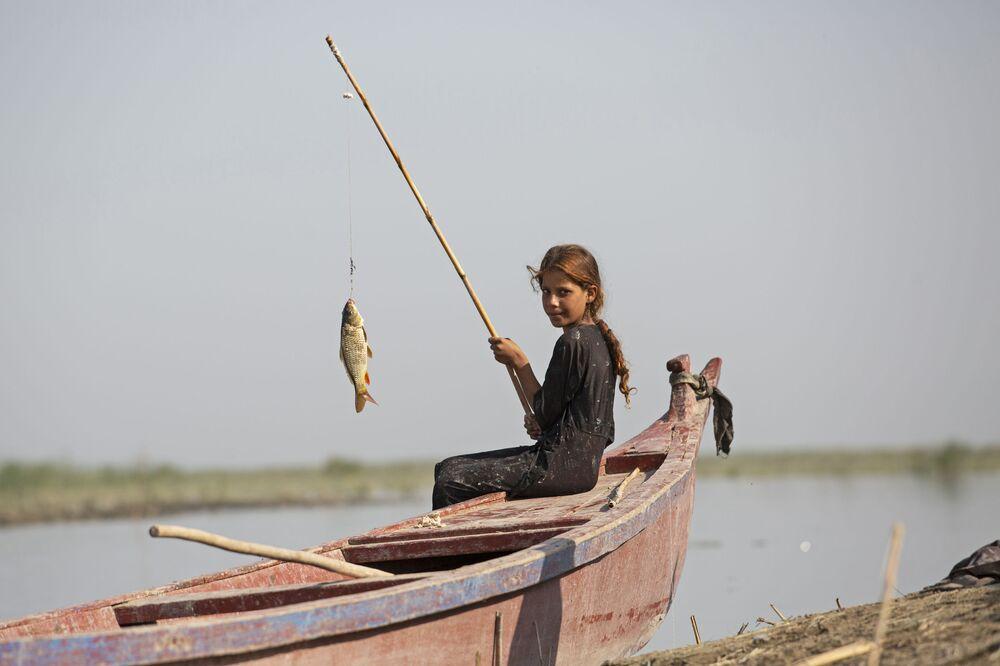 فتاة تصطاد سمكة في مستنقعات منطقة شبايش الجنوبية بمحافظة ذي قار، على بعد حوالي 120 كيلومترًا شمال غرب مدينة البصرة الجنوبية، في 23 سبتمبر/ أيلول 2020.