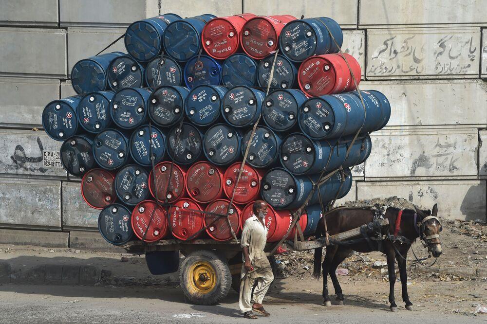 رجل يسير بجوار عربة حصان محملة ببراميل زيت في أحد شوارع لاهور، باكستان 27 سبتمبر 2020