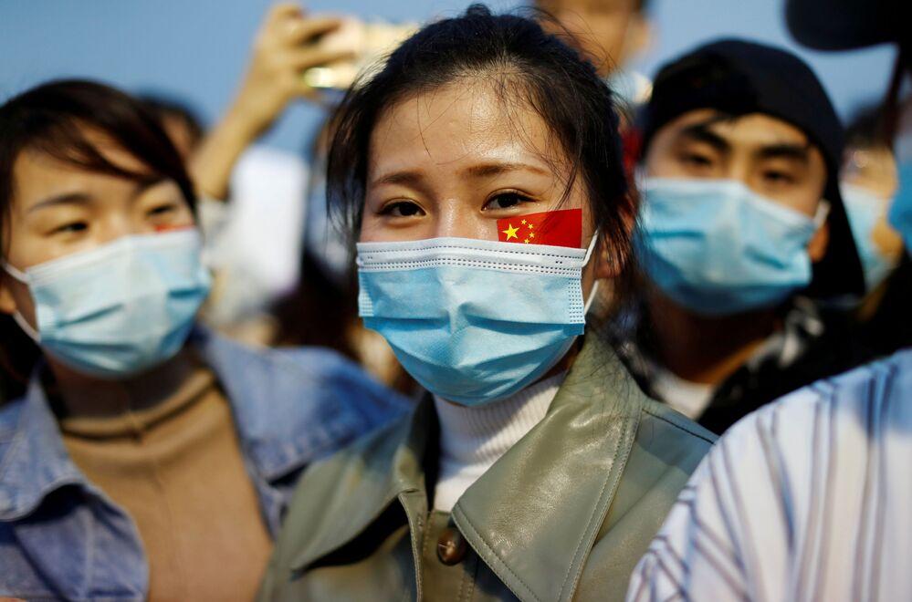 أشخاص يرتدون كمامات طبية، بعد تفشي مرض فيروس كورونا (كوفيد -19)، يحضرون مراسم رفع العلم في ميدان تيانانمن في اليوم الوطني للاحتفال بالذكرى الـ71  لتأسيس جمهورية الصين الشعبية، في بكين  الصين، 1 أكتوبر 2020
